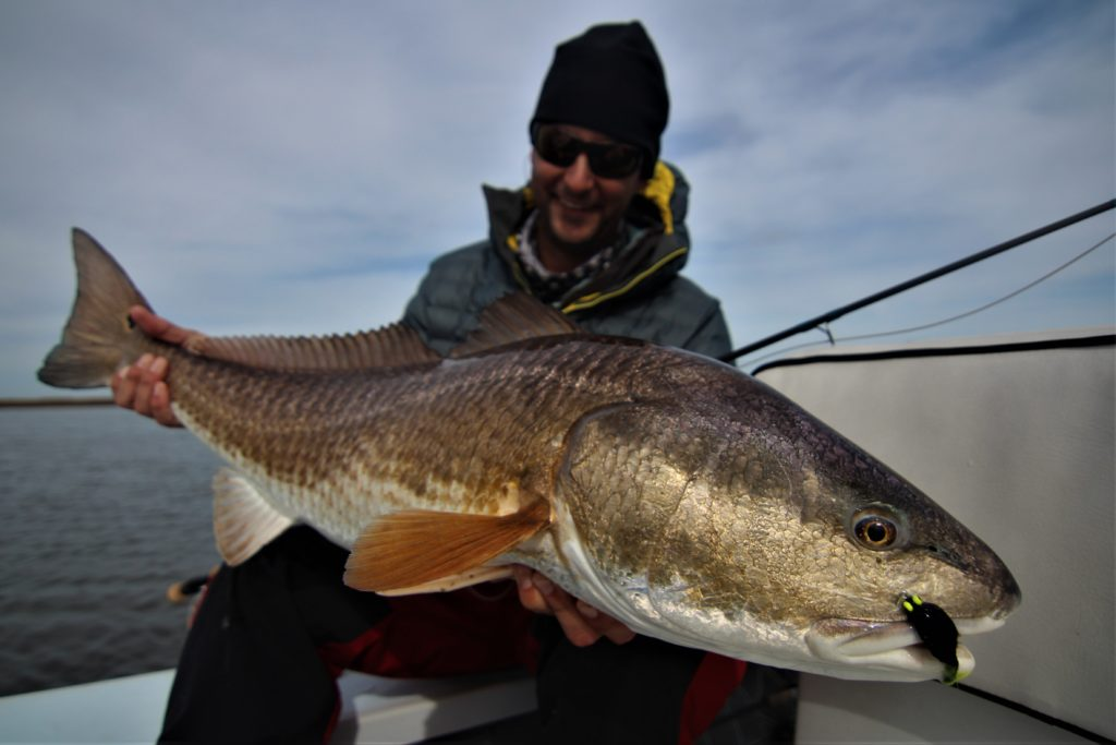 Mike proudly showing off an epic Louisiana Marsh Redfish he caught on fly.