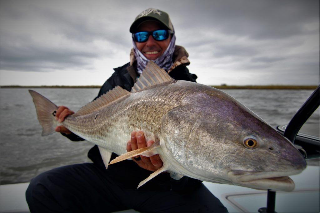 Manny smiling with his biggest redfish in the Louisiana Marsh.